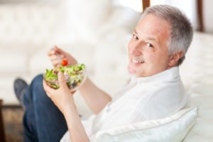 Mature man eating a healthy salad sitting on his couch